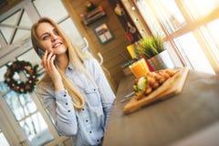 Mädchen, das am Handy spricht und im gemütlichen Café sitzt am Tisch mit den süßen Waffeln und dem Orangensaft sich entspannt Lizenzfreie Stockbilder