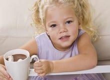 Mädchen, das heiße Schokolade aus Becher heraus trinkt Stockbilder