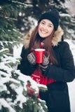 Mädchen, das heißen Tee im Winterwald trinkt Stockfotos