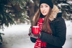 Mädchen, das heißen Tee im Winterwald trinkt Stockfotografie