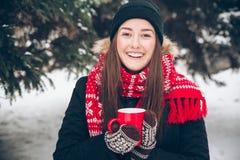 Mädchen, das heißen Tee im Winterwald trinkt Lizenzfreie Stockbilder