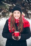 Mädchen, das heißen Tee im Winterwald trinkt Stockfoto