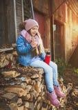 Mädchen, das heißen Tee von der Thermosflasche trinkt lizenzfreie stockfotos
