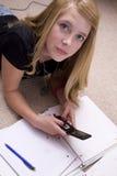 Mädchen, das Heimarbeit mit Handy tut Stockfotos