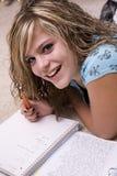 Mädchen, das Heimarbeit und das Lächeln tut Stockfoto