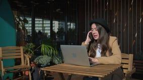 Mädchen, das heraus durch Café mit Geräten hängt stock footage