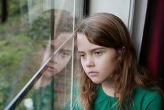 Mädchen, das heraus ein Fenster mit einem traurigen Ausdruck schaut lizenzfreies stockbild