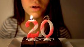 Mädchen, das heraus eine 20. Geburtstagskerze durchbrennt Lizenzfreie Stockfotografie
