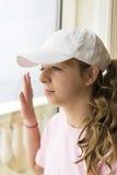 Mädchen, das heraus Erholungsortfenster schaut Stockfotos