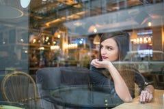Mädchen, das heraus Fenster im Café schaut stockbilder