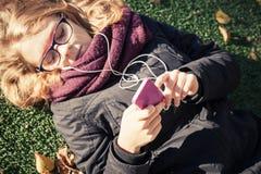 Mädchen, das in herbstlichen Park legt und Smartphone verwendet Stockfotos
