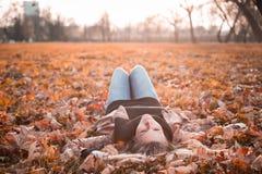 Mädchen, das herein auf dem Herbstlaub zur Sonne liegt Lizenzfreie Stockfotografie