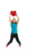Mädchen, das Herzkissen hält Stockfotografie