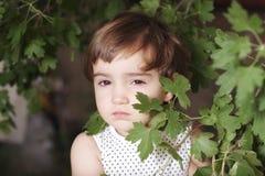 Mädchen, das hinter Blättern sich versteckt Stockfoto