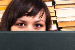 Mädchen, das hinter Buch sich versteckt Stockfoto