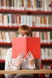 Mädchen, das hinter dem Buch sich versteckt Lizenzfreie Stockfotografie