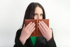 Mädchen, das hinter dem Buch sich versteckt Stockfotografie