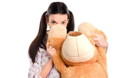 Mädchen, das hinter dem großen teddybear sich versteckt. Stockfotografie