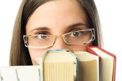 Mädchen, das hinter den Büchern sich versteckt Stockfotos