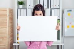 Mädchen, das hinter einem Blatt Papier sich versteckt Lizenzfreie Stockbilder