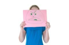 Mädchen, das hinter gefälschtem Gesicht - emotionale Serie sich versteckt Stockfotografie