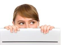 Mädchen, das hinter Laptop schaut Stockbild