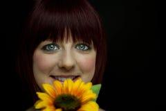 Mädchen, das hinter Sonnenblume lächelt Stockbilder