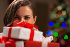 Mädchen, das hinter Weihnachtsgeschenkkästen sich versteckt Lizenzfreies Stockbild