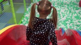 Mädchen, das hinunter Dia auf Spielplatz in der Mitte der Kinder umzieht stock video footage