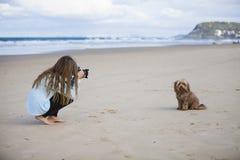 Mädchen, das Hund auf Strand fotografiert lizenzfreie stockfotos