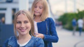 Mädchen, das ihr Mutter ` s Haar tut Lizenzfreie Stockfotos