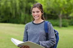 Mädchen, das ihr Notizbuch in einem Park anhält Lizenzfreie Stockfotografie