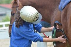 Mädchen, das ihr Pferd auf dem Bauernhof sattelt Stockfotografie