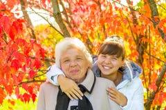 Mädchen, das ihre alte Großmutter im Park umarmt Stockbild