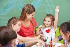Mädchen, das ihre Hand in der Vorschule anhebt Stockfotografie
