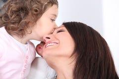 Mädchen, das ihre Mutter küsst Stockfoto