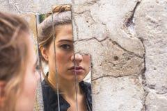 Mädchen, das ihre Reflexion in den Spiegelfragmenten auf der Wand auf Straße betrachtet Stockfotos