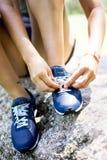 Mädchen, das ihre Schuhe bindet stockbild