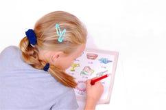 Mädchen, das ihre Schuleheimarbeit tut stockbild