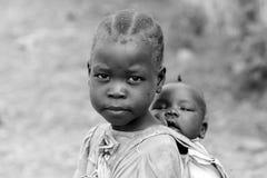 Mädchen, das ihre Schwester in Süd-Sudan trägt Lizenzfreie Stockfotos