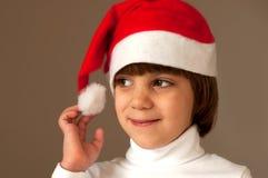 Mädchen, das ihre Weihnachtsschutzkappe berührt lizenzfreies stockbild