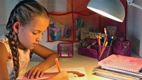 Mädchen, das ihre Zeichnung am Schreibtisch am Abend färbt stock video footage