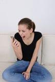 Mädchen, das an ihrem Mobiltelefon schreit Lizenzfreies Stockbild