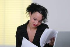 Mädchen, das in ihren Dokumenten schaut stockfoto