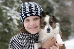 Mädchen, das ihren Hund im Schnee umarmt Stockbild
