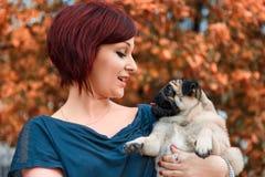 Mädchen, das ihren Pugschoßhund hält Lizenzfreie Stockfotografie
