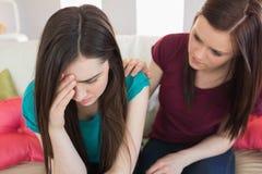 Mädchen, das ihren schreienden Freund auf der Couch tröstet Stockbild