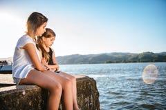 Mädchen, das ihren traurigen Freund auf Dock tröstet Stockfotos