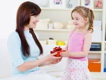 Mädchen, das ihrer Mutter ein Geschenk gibt Stockbild