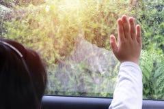 Mädchen, das im Auto sitzt Hände auf dem Autoglas stockfotos